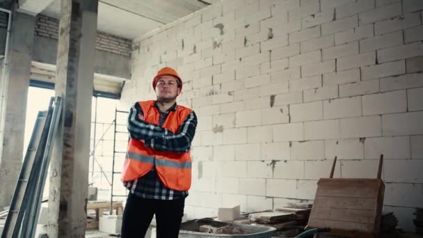 Portrait of a builder man in an orange vest and orange helmet is standing indoors against the backdrop of a construction site holding crossed arms over his chest.