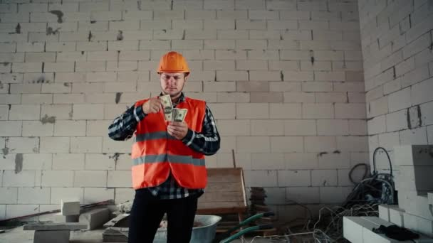A male builder is standing in a building amid a construction site and is slowly scattering money.