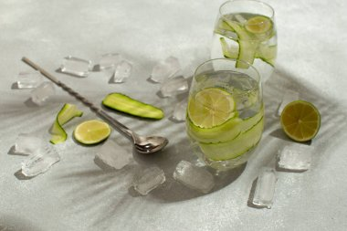 Refreshing detox cocktail with cucumber and limes.Summer cocktail with palm leaves shadow.Close up of healthy drink.