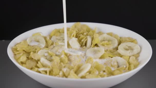 Milch in eine Schüssel mit Cornflakes und Bananen gießen.