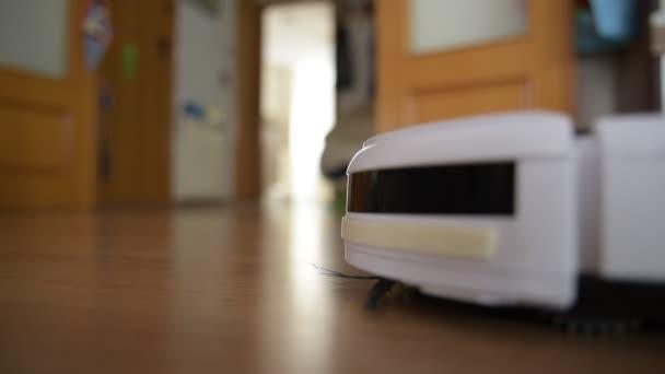 Staubsaugerroboter reinigt den Boden eines Hauses, Blick im Erdgeschoss defokussiert