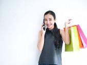 glücklich als eine Frau, die telefoniert und Einkaufstüten hält, Einkaufskonzept.
