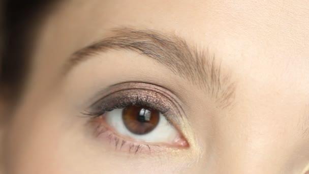 Krásná mladá žena s hnědým okem, dívala se na kameru a blikala