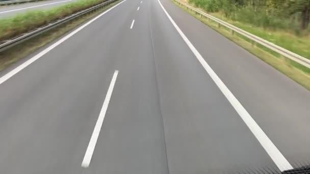 Autobahn Road v Německu. Asfaltová cesta, barevné stromy, slunečná obloha. Cestování autem, z pohledu autobusu ve druhém patře