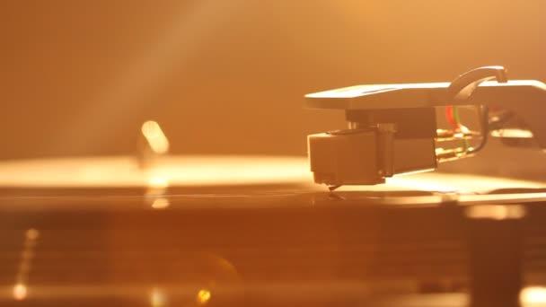 Zárd be a lemezjátszó tűt egy bakelitlemezen. Lemezjátszó bakeliten. Tűt a forgó fekete vinil. Háttérvilágítás