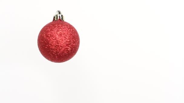 Vánoční a novoroční červený ples. Rotující dekorace na bílém pozadí. Veselé Vánoce a šťastný nový rok!