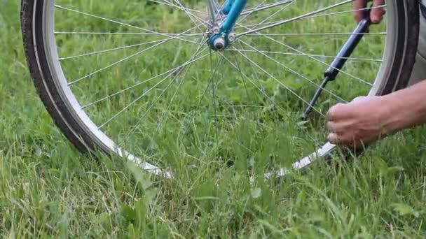 Pumpování kola na kole. Mužské ruce odšroubují uzávěr z kol kola a pumpují. Pohled zblízka