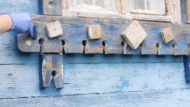 Malování dřeva. Ruka v modré gumové rukavici barvy dřevěné okenní rám se štětcem Close-up. Domácí dílna, ruční práce, ruční práce