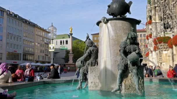 München, Deutschland - 25. Oktober 2017: Touristen in der Nähe von Bronze Brunnen mit Fisch auf dem Marienplatz