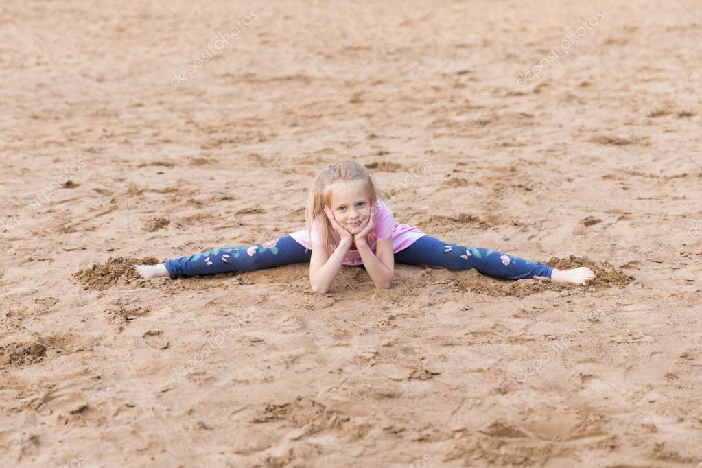 Little blonde girl stretches on the sand outdoors