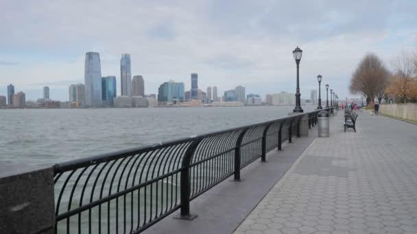 Trénink běžců na pěší procházce podél řeky Hudson na vrcholu centra Manhattanu s mrakodrapy Jersey City v pozadí v zimním oblačném dni