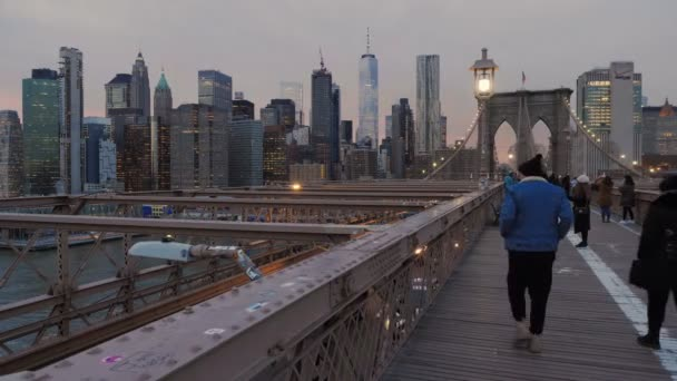 NewYork, January, 2020 - People walking on the Brooklyn Bridge at dusk with skyscrapers and the lights of Manhattan in the background and the car traffic below them