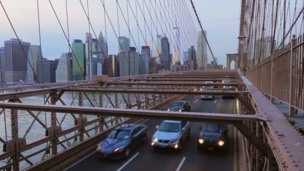 Auta jedoucí po Brooklynském mostě směrem k Brooklynské čtvrti s mrakodrapy Manhattanu v pozadí a propletením tyčí a trámů mostu tvořících mřížku