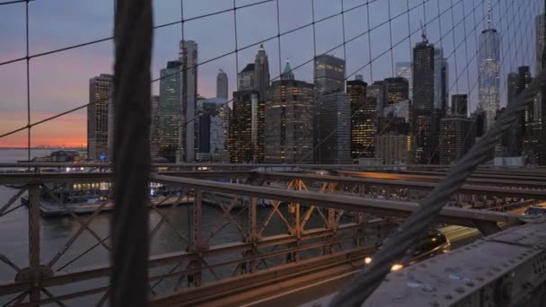A jobb oldali kameramozgás a manhattani felhőkarcolókkal és az East River-rel a Brooklyn-híd kábel- és fémgerendáiban, napnyugtakor