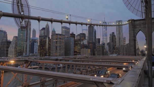 Blick auf die Wolkenkratzer und Lichter von Manhattan von der Brooklyn Bridge bei Sonnenuntergang mit Autos, die die Brücke in der Gasse unter der Fußgängerzone entlangfahren