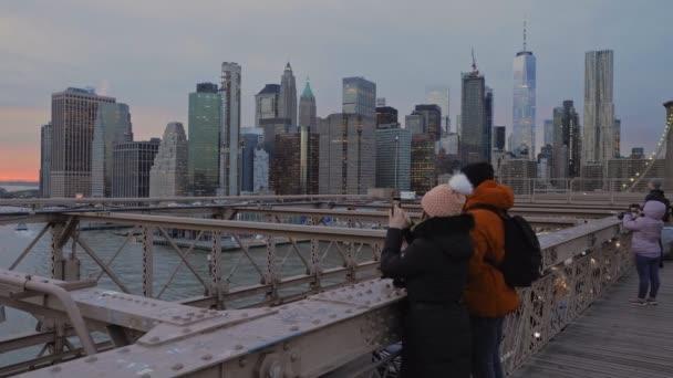 NewYork, 2020 január - Egy fiatal pár fotózza a naplementét New York East River felett a Brooklyn hídról egy hideg téli napon