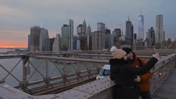 NewYork, 2020 január - Egy fiatal pár szelfizik a Brooklyn hídon az East River feletti naplementét és Manhattan megvilágított felhőkarcolóit használva háttérként