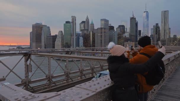 New York, leden, 2020 - Mladý pár fotí a selfies na Brooklynském mostě pomocí západu slunce nad East River a osvětlených mrakodrapů Manhattanu jako pozadí