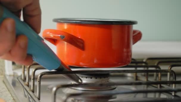 Der rote Topf steht auf dem Gasherd. Die Hand eines Mannes mit einem blauen Feuerzeug nähert sich, indem er das Feuer unter dem Topf mit einem Funken entzündet. Mann bereitet eine Mahlzeit zu, indem er mit einem Kochlöffel im Topf rührt