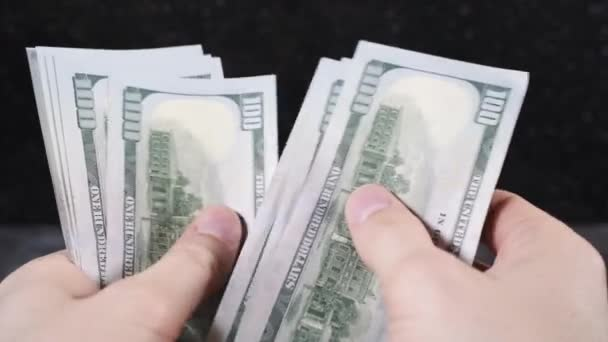 white-skinned man counts dollars with his hands