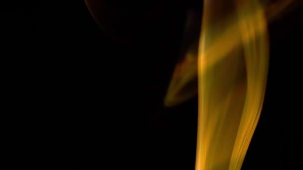 Zlatá hnědá kouř stoupající na černém pozadí
