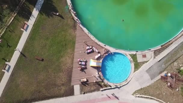 Aerial view sinking down and spinning on small children who play and bathe in a special childrens pool with a small inflatable water slide under the supervision of parents next to a large adult pool