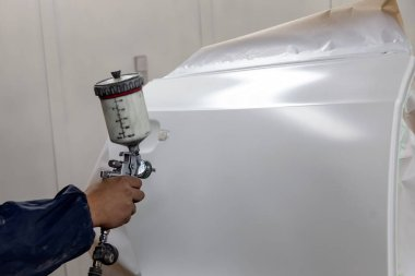 A male worker paints with a spray gun a part of the car body in white after being damaged during an accident. Door from the vehicle during the repair in the workshop.