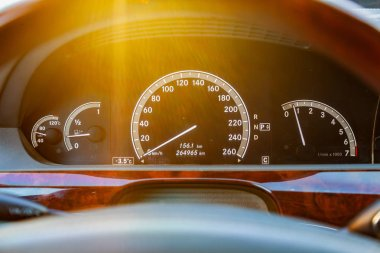 Close-up of a dashboard with elements of a tree in a car's design with a tachometer and speedometer denote fuel level and measuring the engine speed and revolutions on a black background in sunlight.