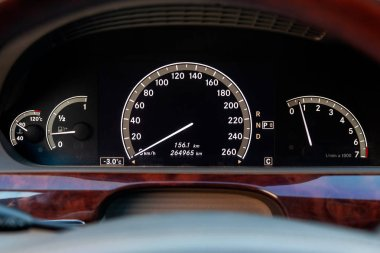 Close-up of a dashboard with elements of a tree in a car's design with a tachometer and speedometer indicating fuel level and measuring the engine speed and revolutions on a black background