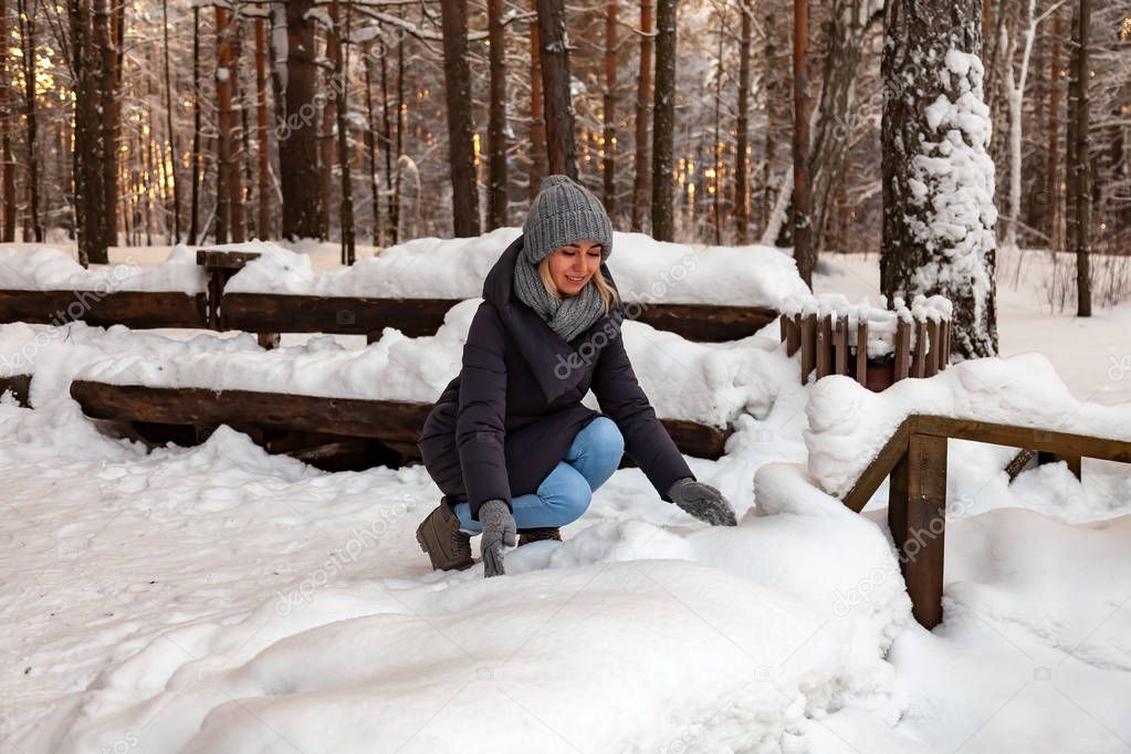 The blonde girl in a gray hat and gloves and a winter jacket squatted down and playing with the snow tossing it up in the forest on the background of a wooden bench.