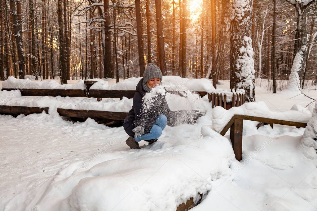 A blonde girl in a gray hat and gloves and a winter jacket squatted in front of a snowdrift and playing with the snow tossing it up and smiling in the forest against the background of a wooden bench.