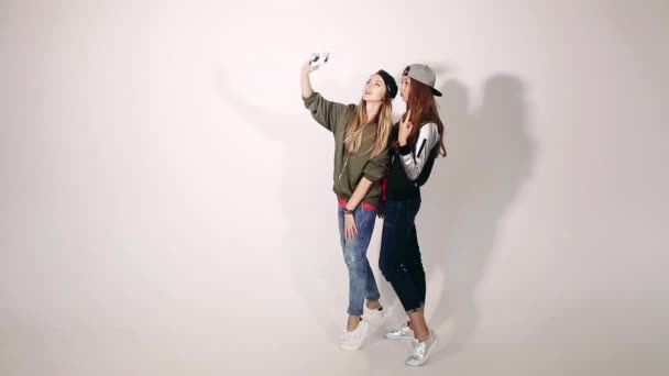Beautiful and fashionable blondie and brunette girls, having fun, making photo together and posing on white background at studio. Swag sisters in stylish clothing, taking self portrait on call phone.
