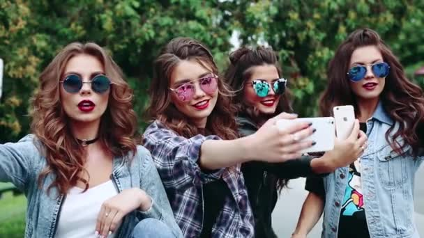 Group of beautiful and fashionable brunette girls making self portrait at smart phones.