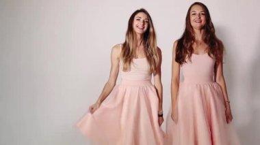 3a59f779f22e80 Vooraanzicht van twee aantrekkelijke en stijlvolle meisjes hun uitlopende  rokken zwaaien
