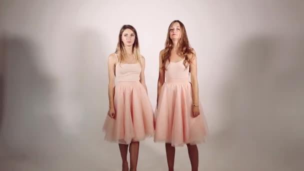 Ragazze gira intorno e gonne volumed rosa dal vento e dal movimento delle ragazze. Due ragazze belle e dolce con capelli lunghi balli contro grigio studio backgound. Concetto di shopping.