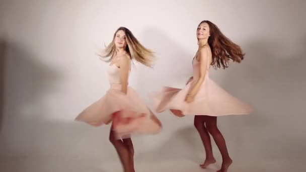 Attractive young girls twirling and whirling in studio with white background. Adorable and trendy slender models wearing pastel pink flared skirts, posing and throwing kisses.