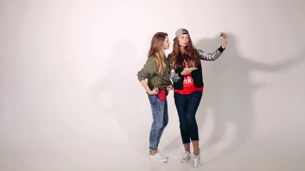 Beautiful and fashionable girls having fun and making photo together.