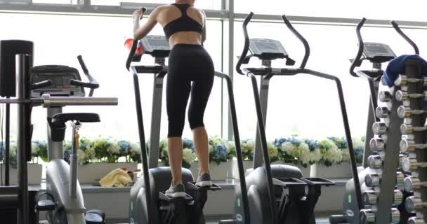 Zadní pohled na fitness žena běží na běžeckém pásu na panoramatické okno, nosí v černém oblečení. Zdravé sportovní žena dělá kardio cvičení na běžeckém pásu. Koncepce sportu a zdraví