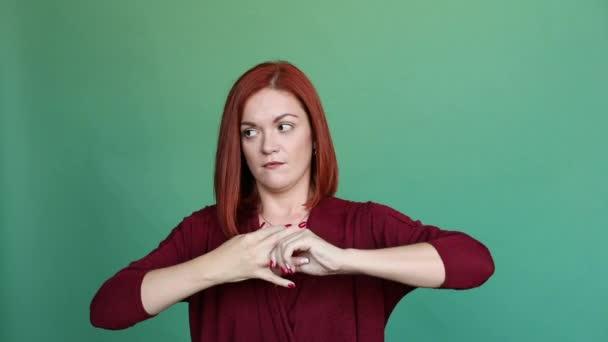 Donna dai capelli rossi che propone allo studio su sfondo verde, tira fuori anello da dito