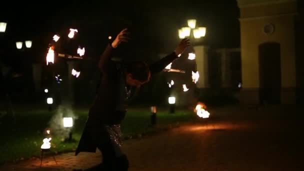 Brave and confident man in black wear turning around stick with fire and dancing. Beautiful night fire show outdoors. Entertainment and dance concept. Restaurant on background.