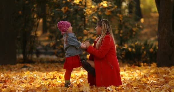 Blond žena v červeném kabátě s pozdravem její dcera v podzimní park.
