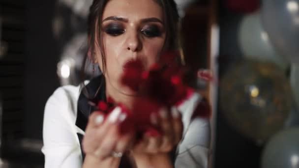 Szép és divatos nő fúj piros konfetti-kamera-kezében.