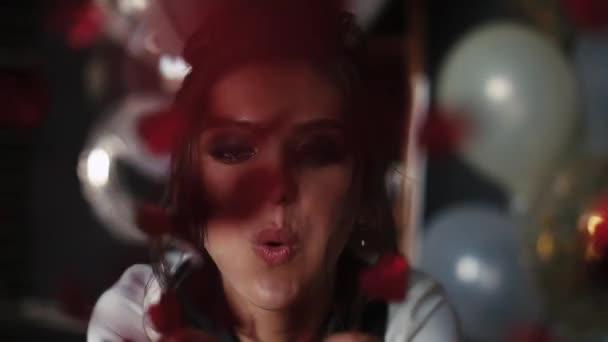 schöne und modische Frau bläst rotes Konfetti an der Hand in die Kamera.