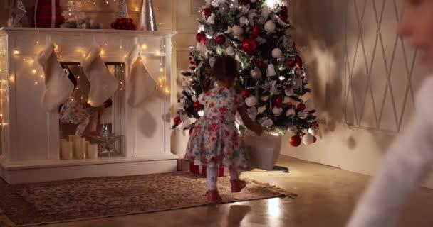 Děti vánoční dárky pod vánoční stromeček.