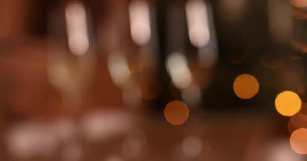 Sektgläser stehen im Hintergrund eines verschwommenen Zimmers mit einem geschmückten Weihnachtsbaum.