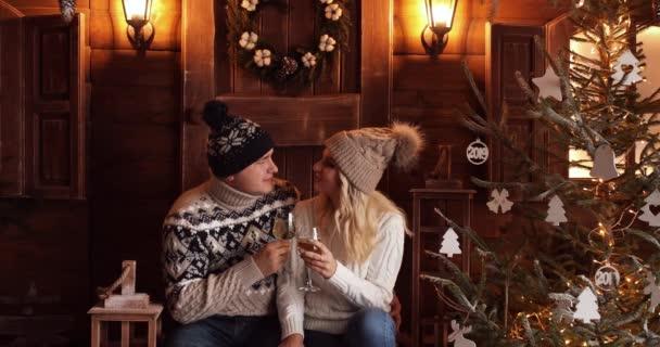 Šťastný pár v zimě oblečení přípitky šampaňským a slaví Nový rok.
