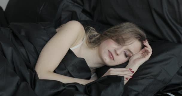 Portrét atraktivní mladá blond žena spí v posteli na polštáři černé a pod černou dekou. Ona mluví a odhodil během spánku v ranních hodinách. Snění v posteli.