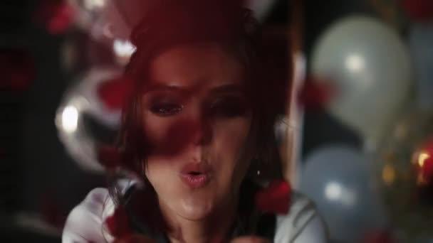 Schöne und modische Frau bläst rote Konfetti in die Kamera von Hand.