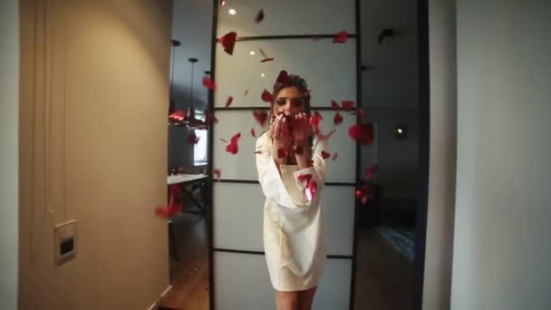 schöne und modische Frau im Hotel mit Make-up und Frisur, die rotes Konfetti mit den Händen in die Kamera pustet. glückliches wunderschönes Mädchen im Bademantel, das irgendeinen Feiertag feiert. Deko-Konzept.