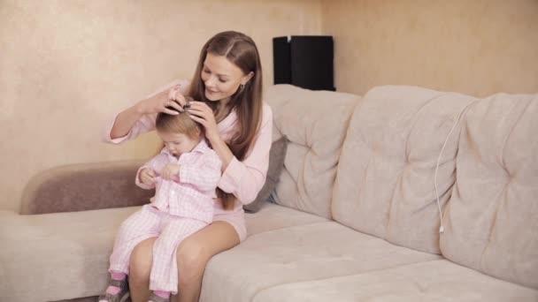 Mladá krásná žena držící na kolenou malé dítě.